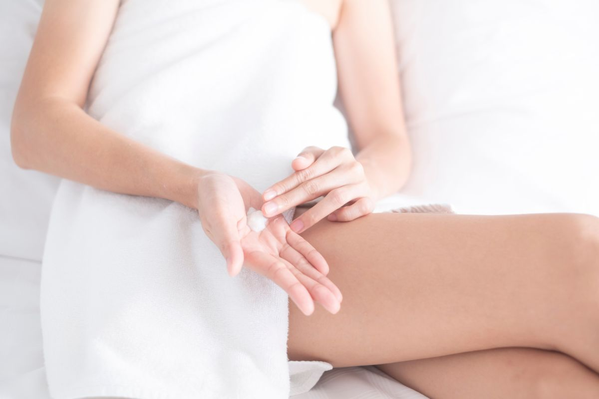 woman applying moisturizing cream lotion on hands beauty concept